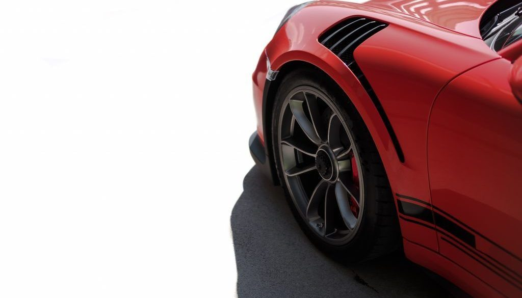 Red sport car front side view, black wheel with metallic silver